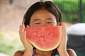 Mädchen isst kernlose Wassermelone bei einer Pool-Party