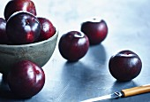 Red plums in a ceramic bowl and next to it
