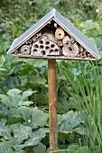 Insektenhotel auf Holzstiel im Gartenbeet