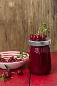 A jar of cherry jam and fresh cherries