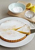 Lemon tart with icing sugar, sliced