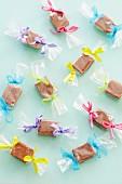 Toffee-Bonbons in Cellophanpapier mit bunten Schleifen (Aufsicht)
