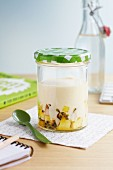 Yoghurt with pineapple, passion fruit and coconut in a screw-top jar