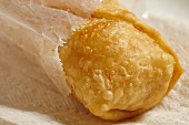 A spring roll in a paper bag (close up)