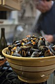 Steamed mussels in a ceramic bowl on a stove