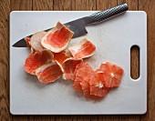 Grapefruitscheiben, Schalen und Messer auf Schneidebrett