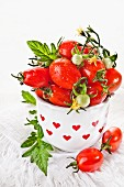 Cherry tomatoes in a vase decorated with red hearts