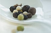Various spices on a spoon: allspice berries and peppercorns
