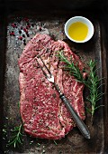Raw, seasoned beef steak on a baking tray