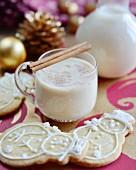 Traditioneller Eierpunsch mit Zimtstangen und Schneemann-Plätzchen (weihnachtlich)