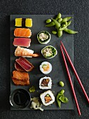 Nigiri sushi, California rolls, maki sushi and sashimi on a stone platter