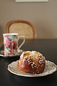 Brioche with sugar nibs and tea in a floral-patterned mug