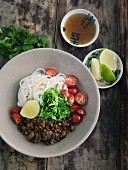 Rice noodles with fried minced meat, tomatoes and coriander in a porcelain bowl on a wooden table