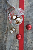 Cinnamon stars in a jar with a flip-top lid next to Christmas tree baubles and a ribbon
