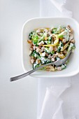 Vegetable salad with broccoli, chickpeas, raisins, yellow peppers and a yoghurt sauce