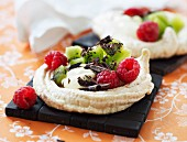 A tartlet with kiwis, raspberries, cream and chocolate curls