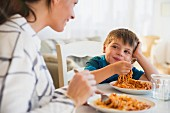 A mother and son eating spaghetti