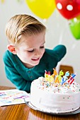 A little boy looking at a birthday cake