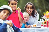 Vier Kinder auf einer Gartenparty