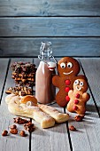 Two gingerbread men, a bottle of cocoa, a bread man and Christmas biscuits on a grey wooden surface