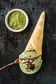 Green tea ice cream with chocolate sauce in a homemade ice cream cone