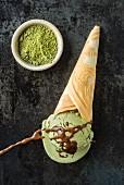 Green tea ice cream with chocolate sauce in a homemade ice cream cone