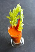 Pepper and orange gazpacho with a stick of celery and sweetcorn