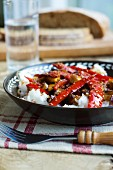 Sweet and sour aubergines with peppers and sesame on a bed of rice