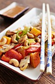 Sweet and sour vegetables with pumpkin, mushrooms and cashew nuts on a bed of rice