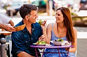 Couple enjoying food in pavement restaurant