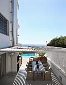 Mit Sonnenschutzlamellen überdachte Terrasse zwischen mehrstöckigem Wohnhaus und Gartenmauer, im Hintergrund das Meer