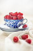 Raspberries in and around a teacup