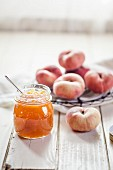 A jar of peach jam and vineyard peaches