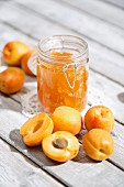 A jar of apricot jam and fresh apricots