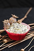 A cupcake with icing sugar, poppy seeds and poppy seed pods