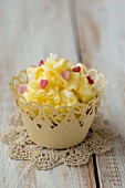 A cupcake decorated with yellow butter cream and sugar hearts on a crocheted doily