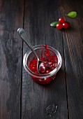 Cranberry sauce in a glass with a spoon on a dark wooden surface