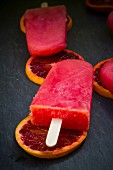 Blood orange ice lollies and blood orange slices on a slate surface