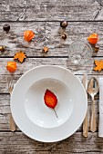 A soup dish on an autumnal laid table
