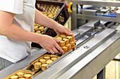 Frau nimmt verpackte Kekse vom Förderband in einer Backfabrik
