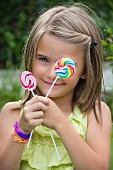 A little girl holding two lollipops