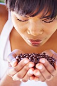 A woman smelling a handful of coffee beans