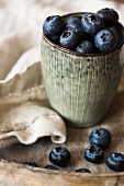 Blueberries in a cup on a wooden tray with a napkin