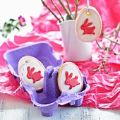 Egg-shaped Easter biscuits decorated with rabbits in an egg box