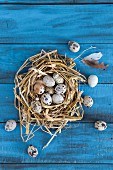 Quail's eggs in a straw nest on a blue wooden surface (seen from above)
