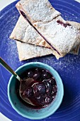 Three slices of blueberry strudel dusted with icing sugar with a bowl of blueberry sauce