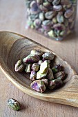 Shelled pistachios on an olive wood spoon
