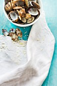 Empty clamshells in a bowl and on a table with grated Parmesan crumbs and a linen cloth