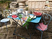 Pans and lids, wild asparagus and basket of tomatoes on pastel blue terrace table