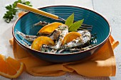 Breaded sardines with orange and bay leaves